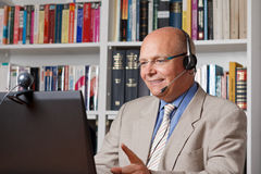 Äldre man med hörlurar och datoren arkivbild