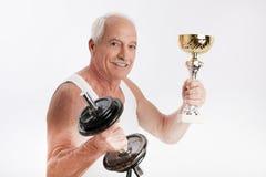 Äldre man med hantlar och trofén royaltyfri foto