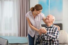 Äldre man med kopp te nära kvinnlig anhörigvårdare hemma arkivbilder