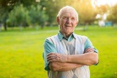 Äldre man med korsade armar Arkivbild
