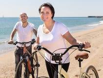 Äldre man med kvinnan i vita skjortor som går med cyklar på arkivbild