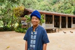 Äldre man med smileyframsidauppehälle i thai by för taditional med farmstay Royaltyfria Bilder