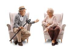 Äldre man och åldringkvinna, i fåtöljsamtal Arkivfoton