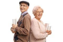 Äldre man och en äldre kvinna med böcker Arkivfoto