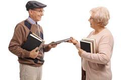 Äldre man och äldre en kvinna som utbyter böcker Royaltyfri Bild