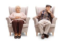 Äldre man och ett äldre kvinnasammanträde i fåtöljer Arkivbilder