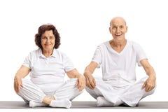 Äldre man och ett äldre kvinnasammanträde på en matt övning Arkivbilder