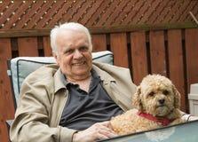 Äldre man och hund arkivbilder