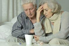 Äldre man och kvinna med influensa arkivfoto