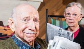 Äldre man och kvinna med tidningen Arkivbild