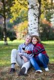 Äldre man och kvinna som fotograferar på telefonen i parkera Arkivfoto