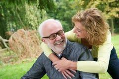 Äldre man och kvinna som utomhus ler fotografering för bildbyråer