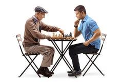 Äldre man och ung en grabb som spelar en lek av schack arkivbild