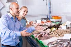 Äldre man och ung flicka som väljer skaldjur Royaltyfria Bilder