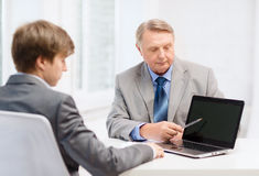 Äldre man och ung man med bärbar datordatoren Arkivbilder