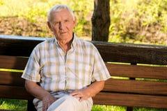 Äldre man på en bänk Arkivfoton