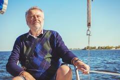 Äldre man på yachten på havet Arkivbild