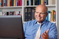 Äldre man som är frustrerad framme av anteckningsboken arkivbilder