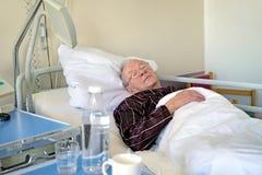 Äldre man som återfår krafter i ett sjukhus Arkivfoto