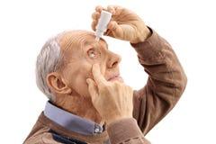 Äldre man som applicerar ögondroppar Royaltyfria Foton