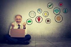 Äldre man som arbetar på datoren genom att använda social massmediaapplikation Arkivbild