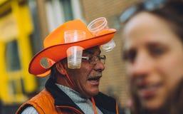 Äldre man som bär den roliga orange ölhatten, festlighet för dag för konung` s Royaltyfria Foton