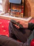 Äldre man som bara bor, med tvfjärrkontroll i hand fotografering för bildbyråer