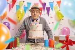 Äldre man som blåser stearinljus på en födelsedagkaka Arkivbild