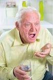 Äldre man som dricker preventivpillerar och vatten royaltyfri foto