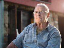 Äldre man som framme sitter hans hus på gryning Arkivfoton