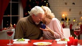 Äldre man som ger smyckengåvaasken till hans fru, kvinna som kysser ömt maken royaltyfria bilder