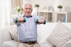 Äldre man som hemma övar Arkivbild
