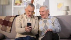 Äldre man som hemma visar det roliga fotoet på åldrig vän för smartphone och att ha gyckel stock video