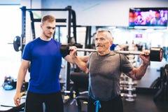 Äldre man som hjälper den höga mannen på idrottshallen royaltyfria bilder