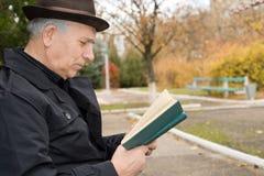 Äldre man som läser och tycker om freden Royaltyfri Fotografi