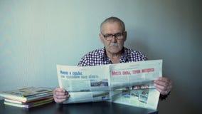 Äldre man som läser tidningen lager videofilmer