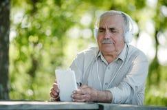 Äldre man som lyssnar till musik på en minnestavla Royaltyfri Foto