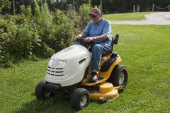 Äldre man som mejar gräs med hans ridninggräsklippningsmaskin Arkivbild