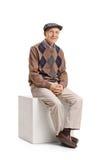Äldre man som placeras på en kub Fotografering för Bildbyråer