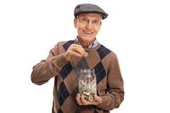 Äldre man som sätter ett mynt in i en krus med pengar royaltyfri bild