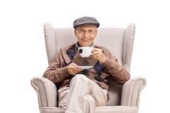 Äldre man som sitter i en fåtölj och dricker en kopp te royaltyfria foton