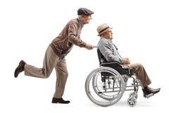Äldre man som skjuter en man i en rullstol arkivbild