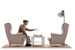 Äldre man som spelar en lek av schack och argumenterar med en tom ar Arkivfoto