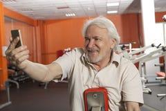 Äldre man som tar en selfie med smartphonen royaltyfri foto