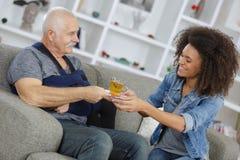 Äldre man som tas omsorg av den unga härliga kvinnan royaltyfria foton