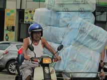 Äldre man som transporterar polystyrenlunchaskar arkivbild