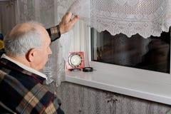 Äldre man som ut plirar till och med fönstret Arkivfoto