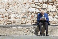 Äldre manläsning och sammanträde på en stenbänk Stenvägg royaltyfri fotografi
