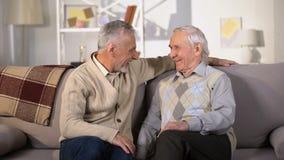Äldre manliga vänner som skrattar och kramar hemmastatt riktigt gammalt kamratskap, vilar stock video