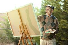 Äldre manmålning på en kanfas Arkivfoton